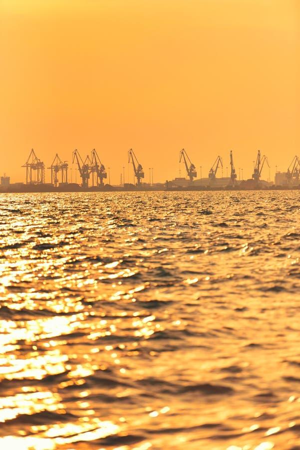 Heavy industrial port equipment, big cranes in sunset light.  stock photo