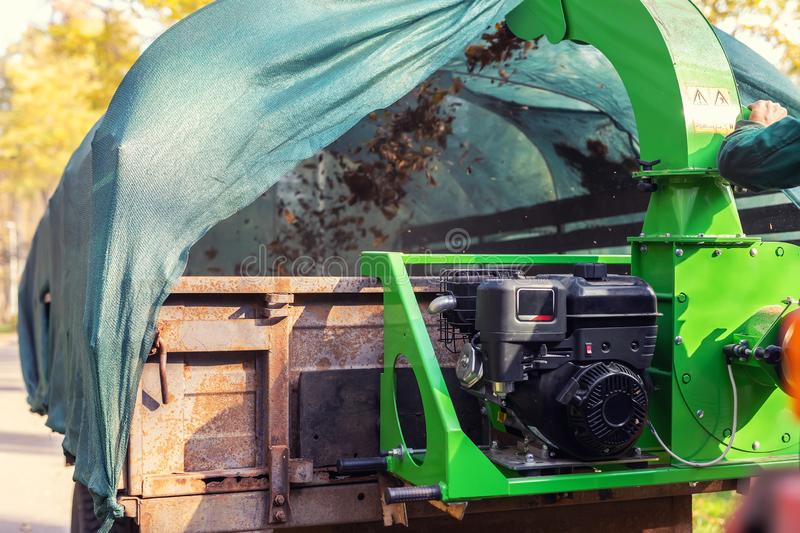 Heavy industrial vaccuum loader loading fallen leaves and junk into truck body. Municipal services cleaning park area removing. Foliage and debris equipment stock photos