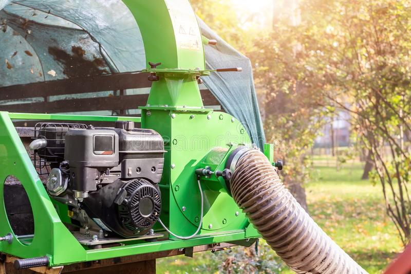 Heavy industrial vaccuum loader loading fallen leaves and junk into truck body. Municipal services cleaning park area removing. Foliage and debris equipment stock photography