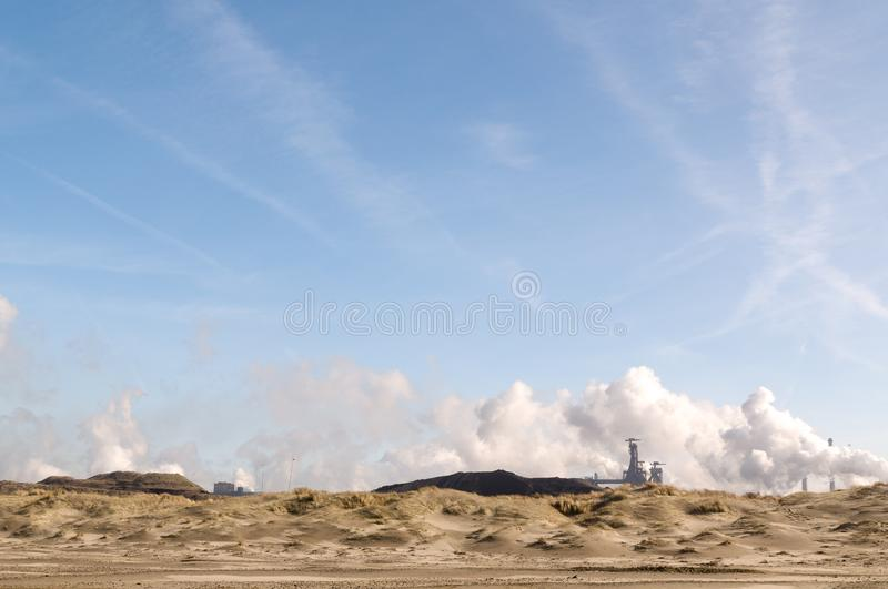 Heavy industry behind the dunes in the Netherlands royalty free stock photo