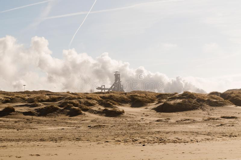 Heavy industry behind the dunes of Velsen in The Netherlands royalty free stock photos