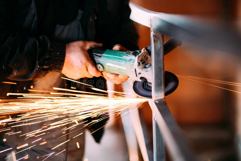 Heavy industry worker cutting steel with angle grinder on construction site stock images