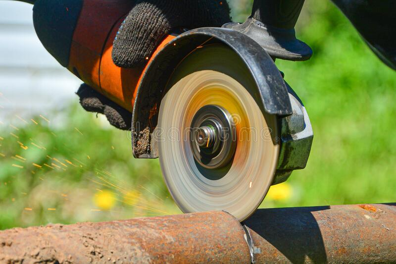 Heavy industry worker cutting steel with angle grinder. Cutting an old rusty pipe. dismantling. close-up royalty free stock photo