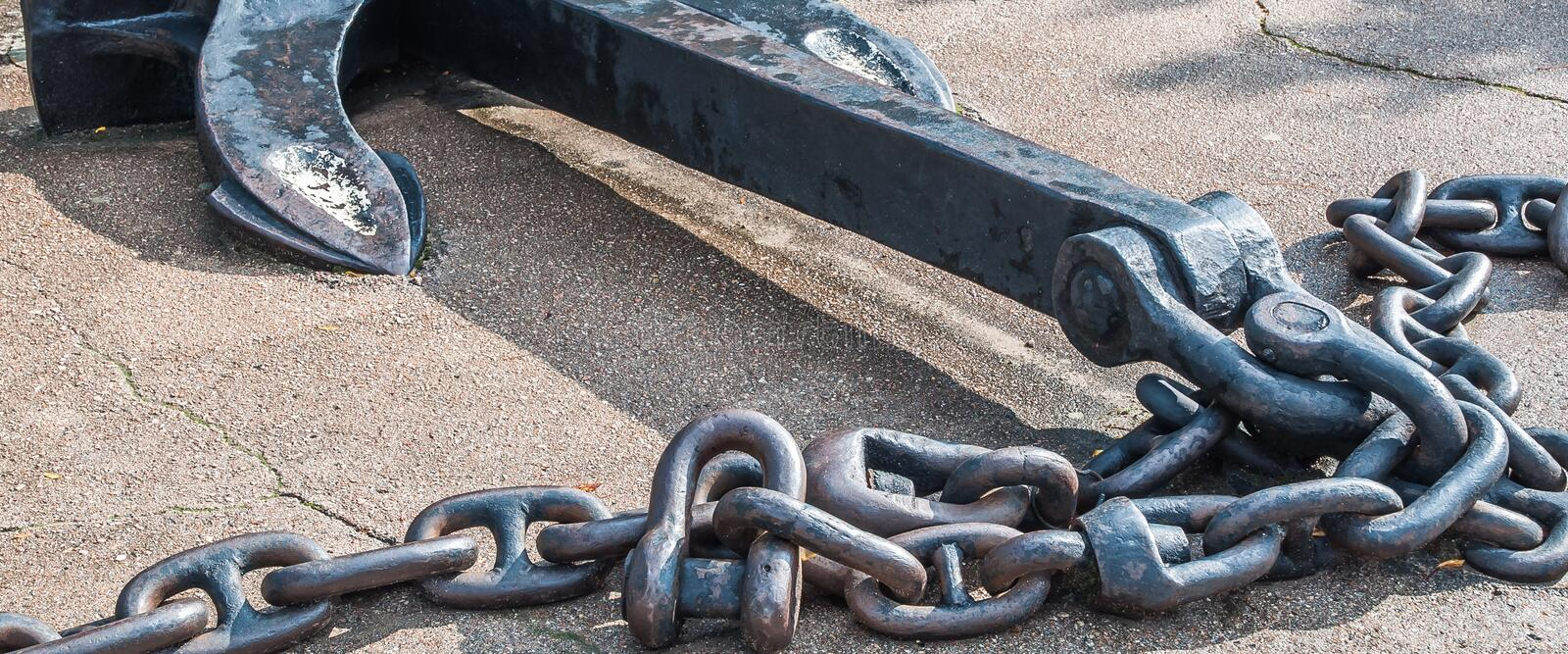 Heavy iron metal ship anchor with chain on gray asphalt. royalty free stock photography