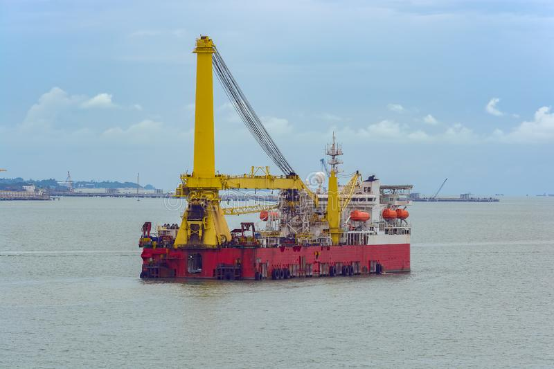Heavy lift derrick and pipelay combination vessel. Self-propelled, dynamically positioned heavy lift derrick and pipelay combination vessel in the Strait of stock image