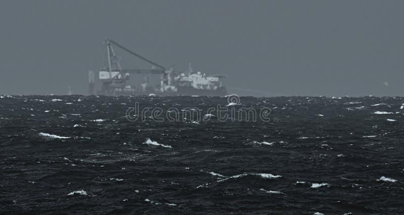 Heavy lift vessel on horizon. Anchor patern royalty free stock photography