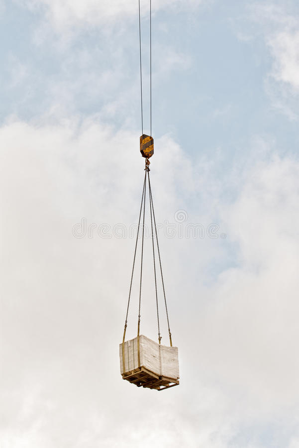 Heavy load of bricks hanging on the crane's hook stock images