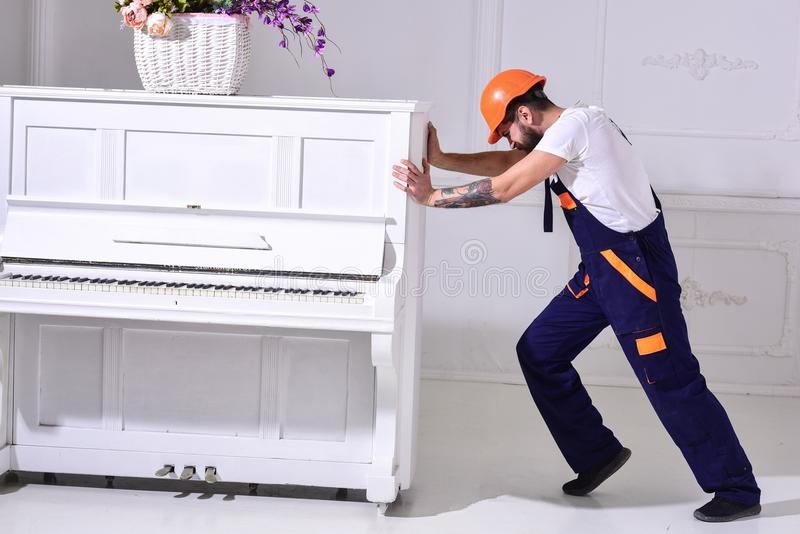 Heavy loads concept. Loader moves piano instrument. Courier delivers furniture, move out, relocation. Man with beard. Worker in helmet and overalls pushes, put royalty free stock images