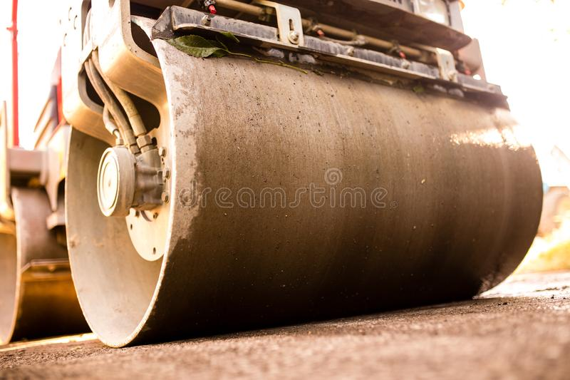 Heavy machine rolls a new asphalt road.  stock images