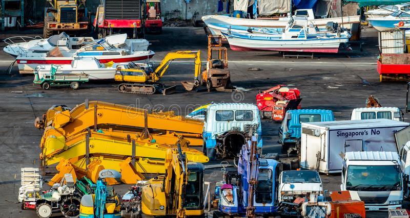 Heavy machinery second hand market. Boat, forklift, agricultural machinery, and electric generator on dirty concrete floor. Warehouse of heavy machinery for royalty free stock photos