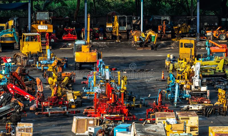 Heavy machinery second hand market. Crane, forklift, backhoe, and electric generator on dirty concrete floor. Warehouse of heavy. Machinery for manufacturing royalty free stock photos