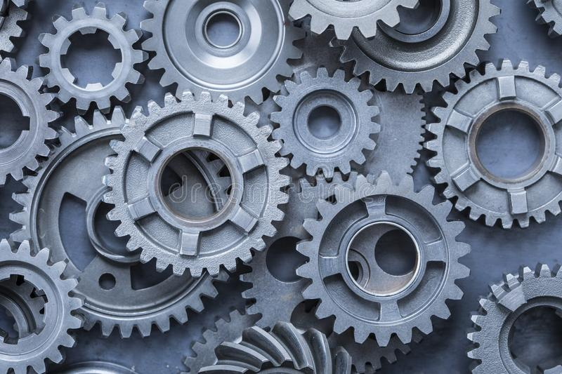 Heavy Metal Gear Background. A large pile of steel gears on a sheet of industrial metal stock image