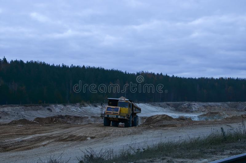 Heavy mining truck driving through the iron ore opencast royalty free stock photography