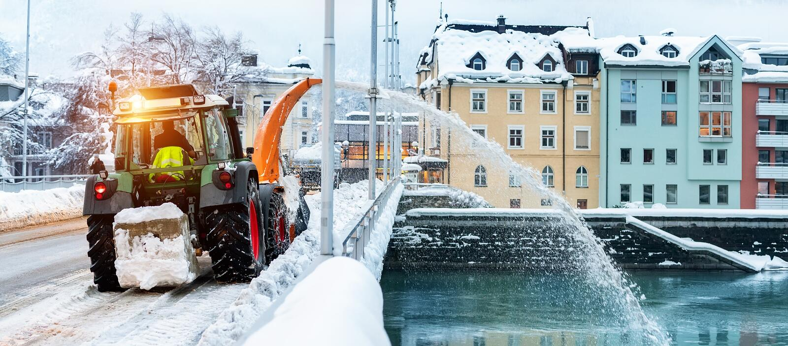 Heavy municipal services machinery removing snow from city streets. Big tractor snowblower blowing snow from bridge road royalty free stock photo