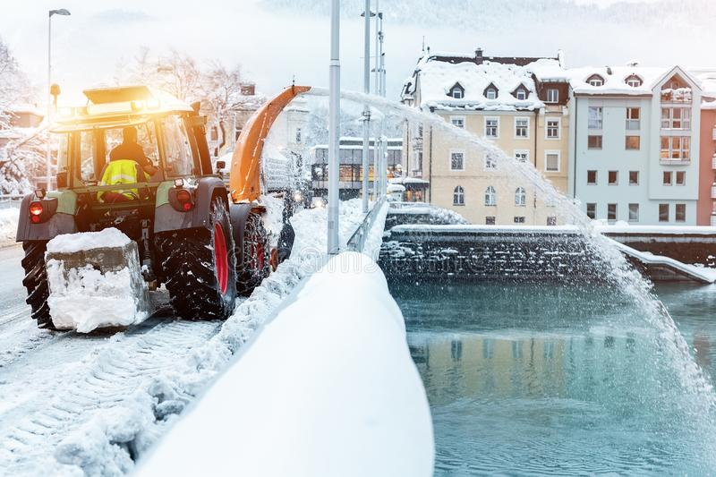 Heavy municipal services machinery removing snow from city streets. Big tractor snowblower blowing snow from bridge road royalty free stock image