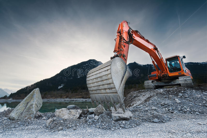 Heavy organge excavator with shovel royalty free stock photography