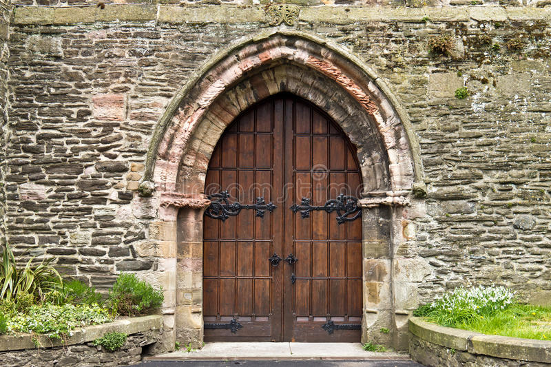 Heavy ornate wooden doors in old stone building royalty free stock photography