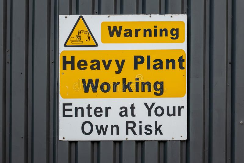 Heavy plant working warning sign on an industrial unit. Warning heavy plant working enter at your own risk sign on the side of an industrial unit stock photos