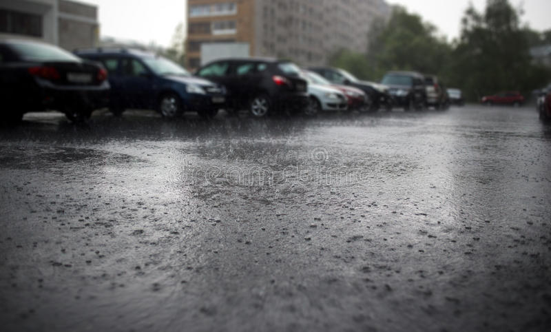 Heavy rain on city street with parked cars at background. stock image