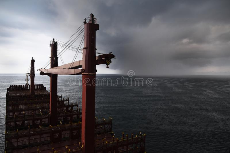 Storm is approaching to cargo ship. Heavy rain cloud is approaching to cargo vessel. No cargo on deck. Three cargo cranes. Taken at Haiphong anchorage area royalty free stock photo