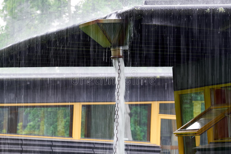 Heavy rain collected in a leader head. Heavy rain ends from a roof in a big reservoir from where it pour out and down a chain made of metal rings royalty free stock image