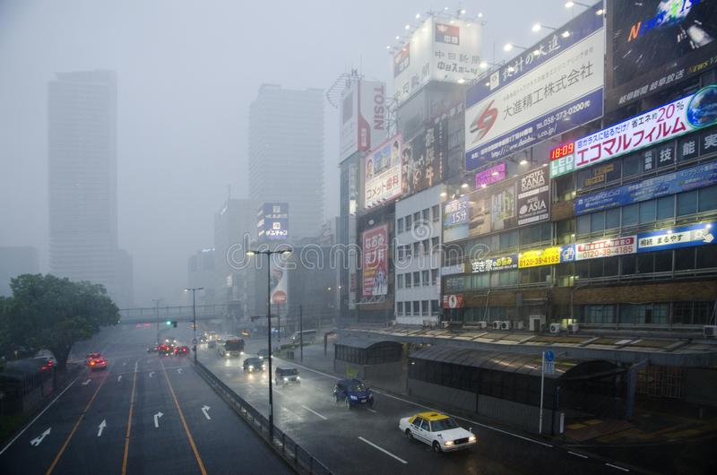 Heavy rain in Gifu city, Japan. Heavy rain during evening in downtown of Gifu city, Japan. Cars driven in rainy and windy weather and advertisement on building stock image