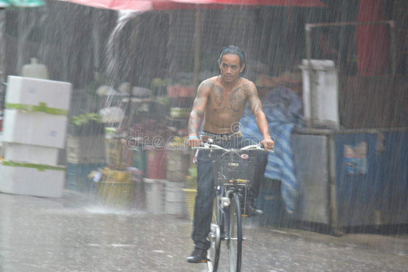 Heavy rain in Mae Sod, Northern Thailand. Motion blur astract of bike rider in the main market of Mae Sod, Northern Thailand, under torrential rain in monsoon stock photography