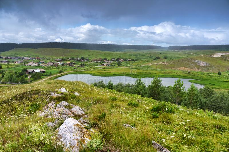 Heavy rain over the Ural village. Lake in the hills. Beautiful colorful sky. Russia royalty free stock photo