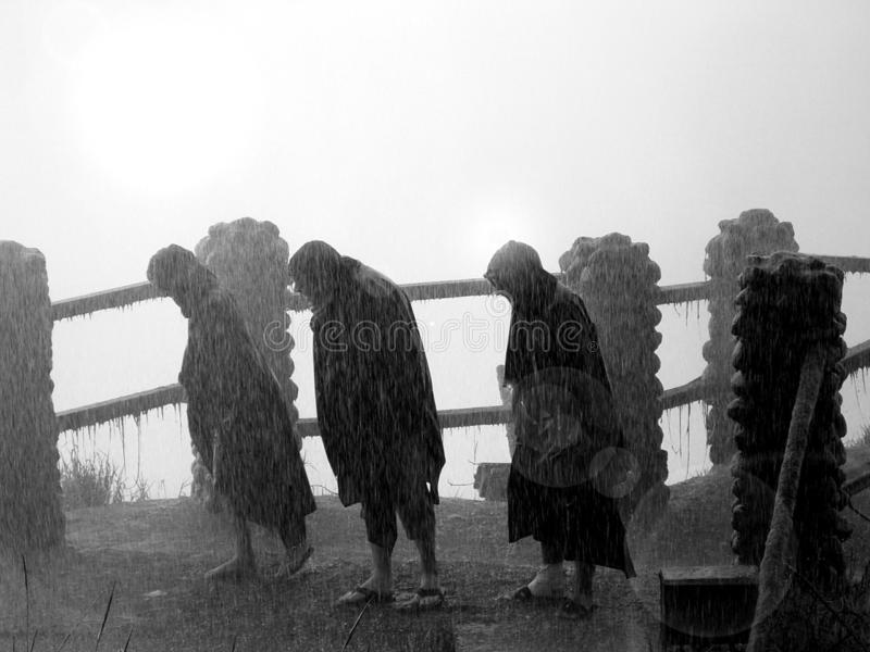 Heavy Rain Storm in Africa. Image of three people in a rain storm at Victoria Falls in Africa stock image