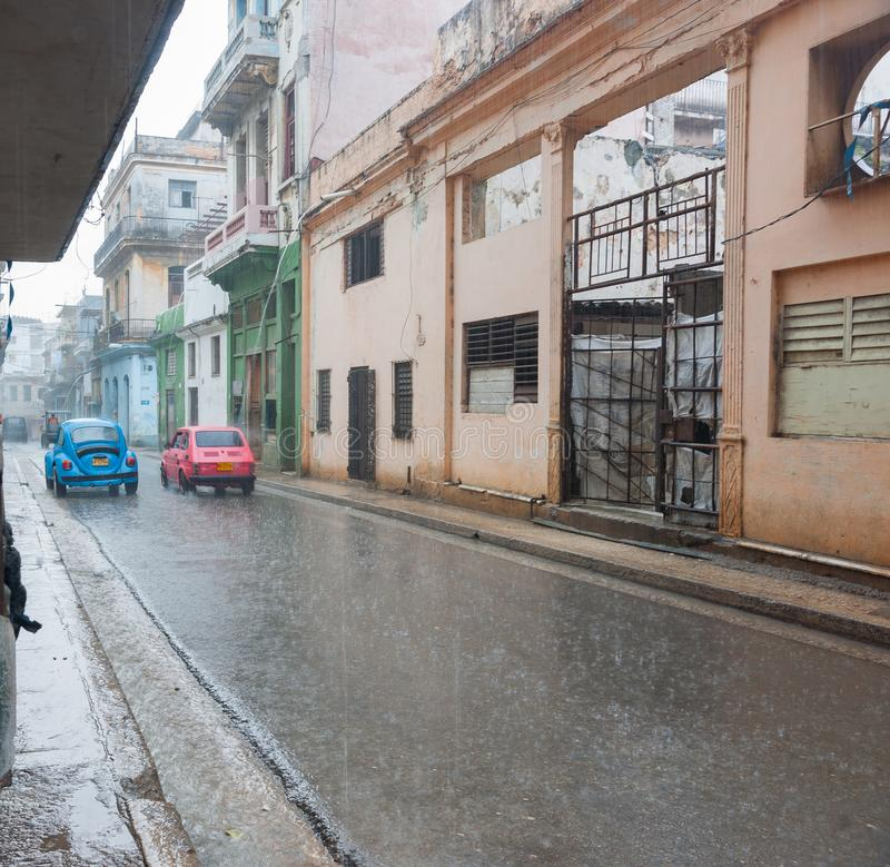 Heavy rain in street of Havana on bright blue VW beetle car and pink Fiat drive away royalty free stock images