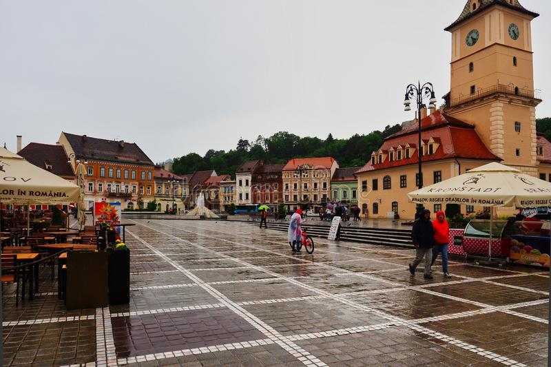 Heavy Rainstorm, Brasov, Romania. Colourful, historic, cobblestones, pedestrian, mall, umbrella, wet, water, pavement, cafe, coffee, shop, flowers royalty free stock image