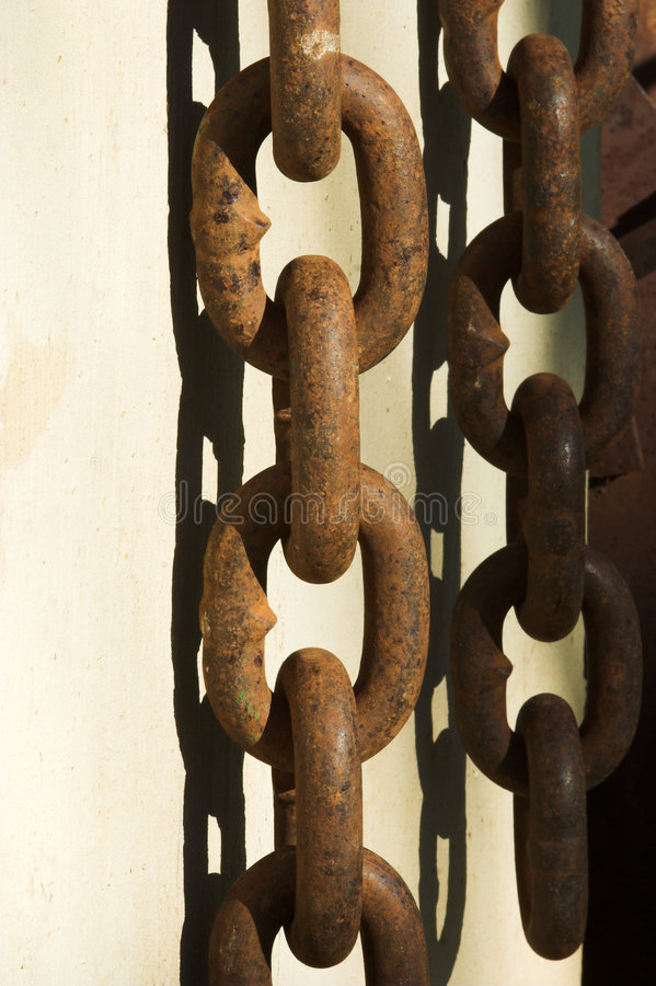 Heavy rusted chain links. Heavy chain links hanging against a wall. The links are rusted and there is a shadow of the links on the wall royalty free stock image