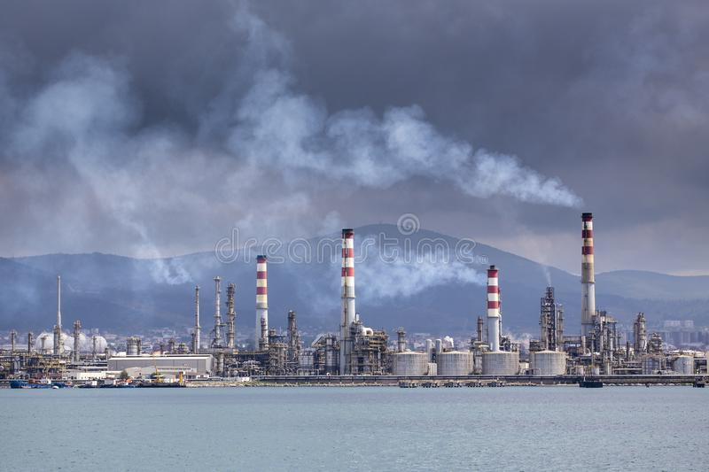 Heavy smoke over an oil refinery. Heavy and gray smoke over an oil refinery royalty free stock photo