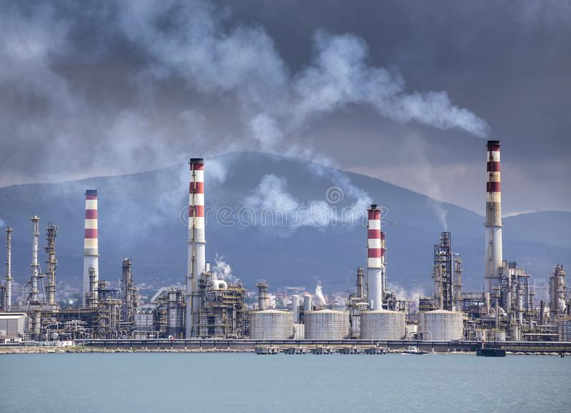 Heavy smoke over an oil refinery. Heavy and gray smoke over an oil refinery stock photo