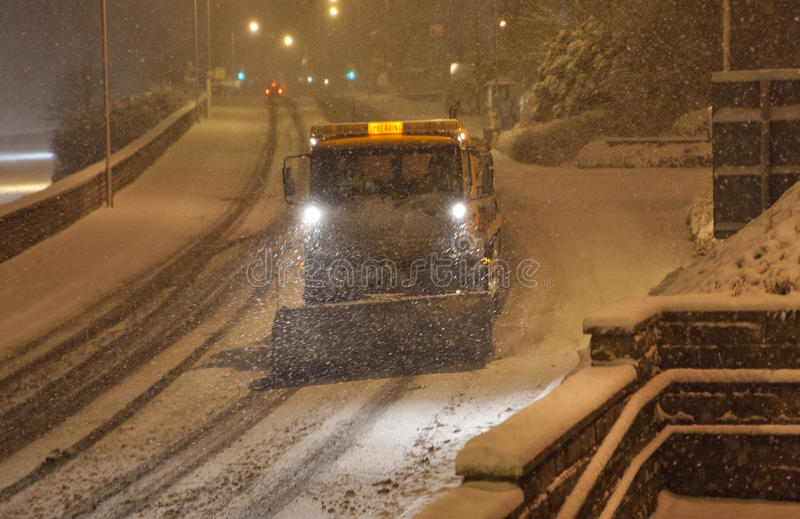 Heavy snow fall with snow plow / gritters. Heavy snow fall at night with passing snow plow / gritters gritting the roads royalty free stock image