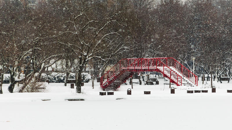 Heavy Snow on the Red Bridge. A metal red bridge which is above a frozen lake on a day with heavy snow royalty free stock images