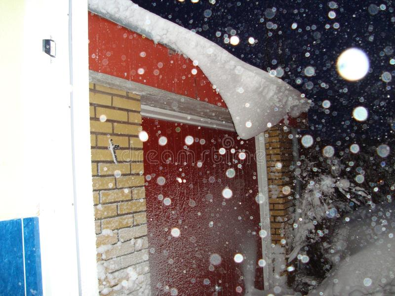 A heavy snow storm is going on so one can hardly see the yellow brickwall of the garage building and the red garage door stock images