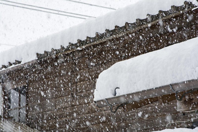 Heavy snow. Wooden building piled heavy snow in winter royalty free stock image