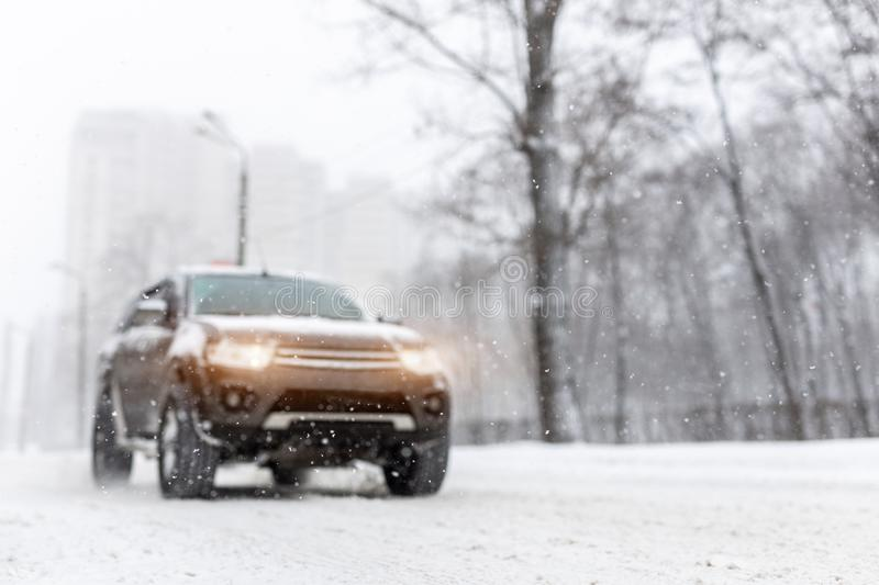 Heavy snowfall and blurred SUV awd car on road. 4wd vehicle on city street at winter. Seasonal roadside assistance concept. Copyspace royalty free stock photo