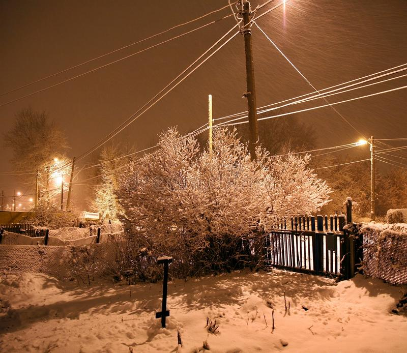 Heavy snowfall at night in the countryside, flying snow. Winter cottages in country landscape at night with glowing lamp light royalty free stock image