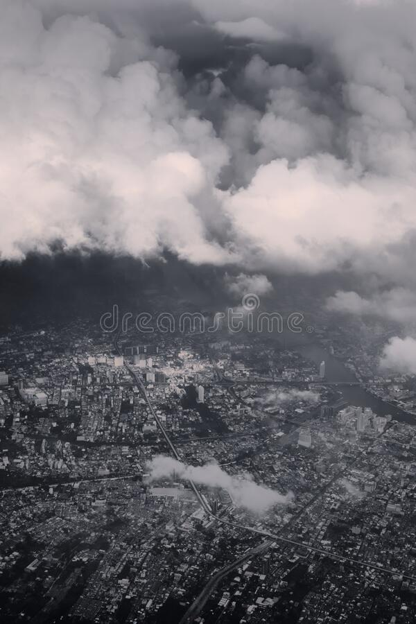 Heavy storm clouds looming over Bangkok, Thailand. Black and white color toning vintage effect. Heavy storm clouds looming over Bangkok, Thailand. Black and royalty free stock photo
