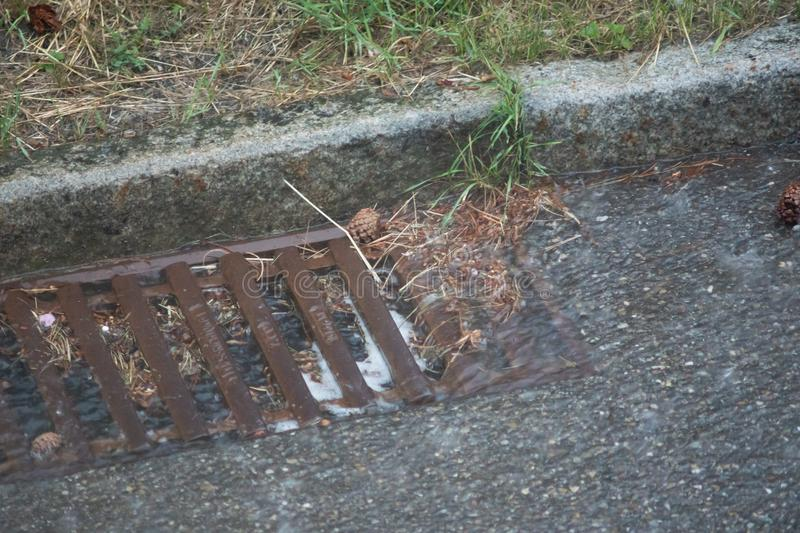 Heavy summer rain and the drain clogged - detail. Heavy rain and the drain clogged royalty free stock image