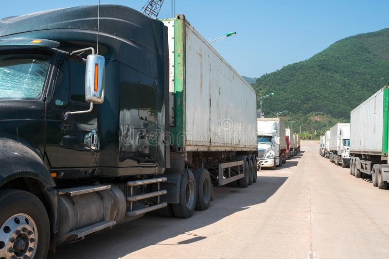 Heavy trucks loaded with goods trailers, parked in waiting area on state border crossing in Vietnam.  royalty free stock image