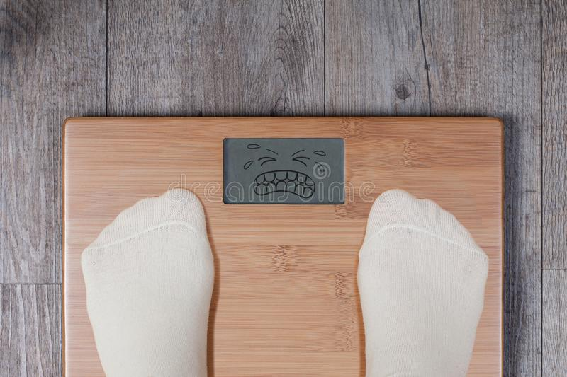 Heavy weight - display shows emoticon face suffering reaction royalty free stock images