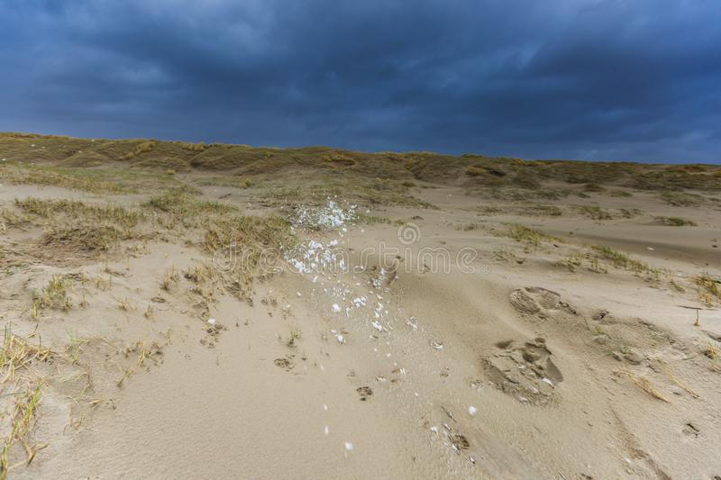Heavy Wester storm to Dutch North Sea coast blows foam caused by surf breakers stock images