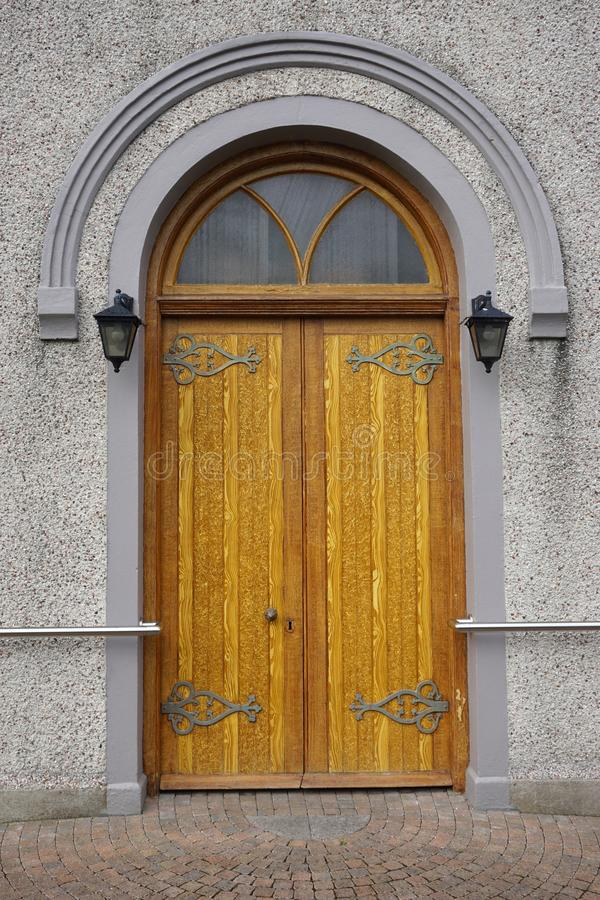 Heavy wooden arched door with ornate hinges royalty free stock photos