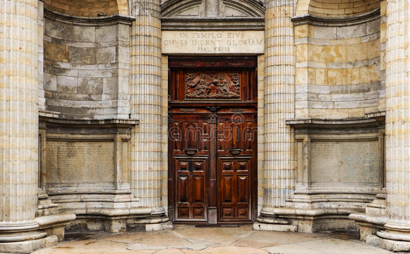 Heavy wooden double door outside of an old church with religious reliefs and inscriptions. This is the entrance of the old St. Nizier christian church in Lyon royalty free stock photo