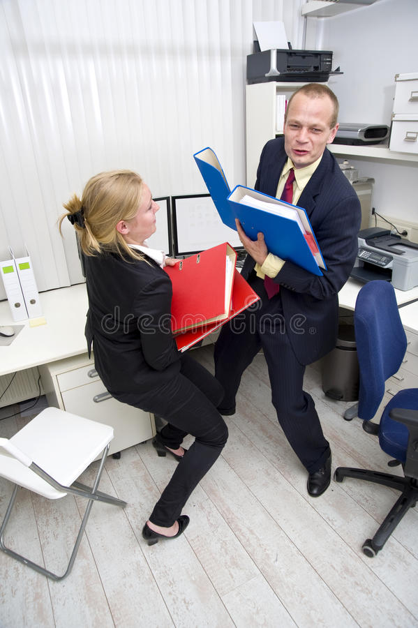 Heavy Workload. Two businesspeople scrambling to carry a heavy workload, represented by thick dossiers stock photo