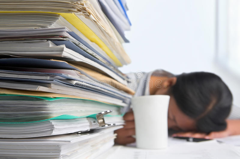 Heavy workload. Concept with pile of paper and woman on background. Selective focus royalty free stock photography