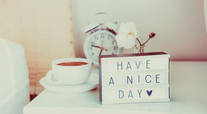 Heb een aardig dagbericht op aangestoken vakje, wekker, kop van koffie en bloem op de bedlijst in zonlicht Goedemorgenstemming royalty-vrije stock fotografie